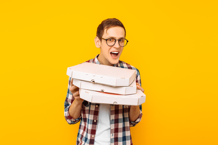 man holding a box of pizza on a yellow background, a happy man with a pizza in his hands