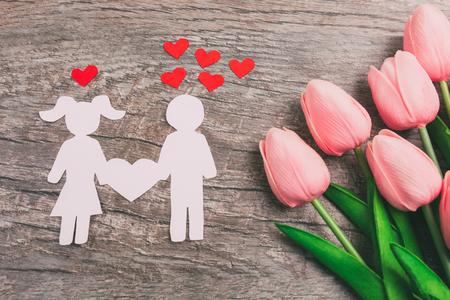 La ragazza e il ragazzo sono ritagliati dalla carta, una coppia di innamorati su uno sfondo di legno, sullo sfondo di un mazzo di tulipani rosa. San Valentino Archivio Fotografico