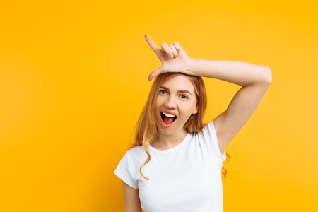the girl shows the gesture of a loser or loser, in a white t-shirt with a grin on his face, on a yellow background