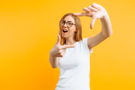 Beautiful young girl with glasses, in a white T-shirt, making a camera frame with fingers, on a yellow background