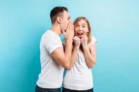 Un homme chuchote à l'oreille d'une femme, lui disant quelque chose de secret, une bonne nouvelle, sur fond bleu.