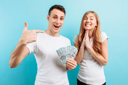 Photo of a happy young couple in love, man and woman, dressed in white T-shirts, holding money in their hands, on a blue background