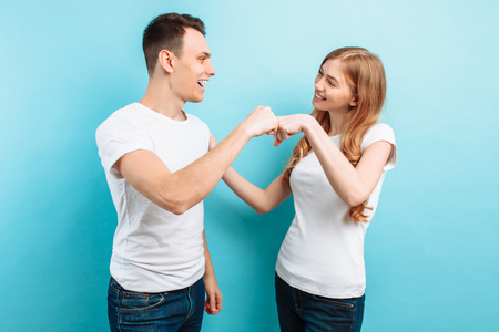 Portrait of friendly young men and women in white t-shirts laughing and giving five, isolated on light blue background