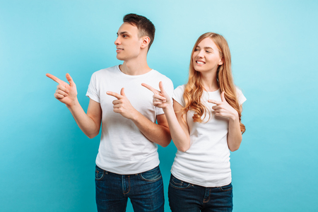 Portrait of a cheerful young couple, man and woman pointing fingers at space for text, isolated against light blue background Banco de Imagens