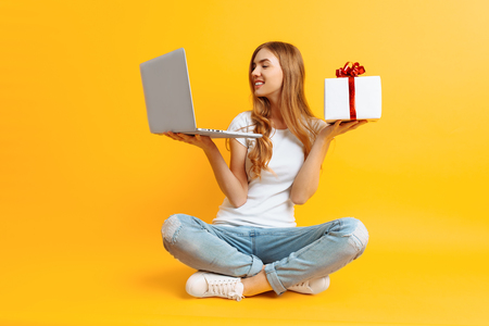 Portrait of an excited girl in a white T-shirt sitting on the floor with a laptop and a gift box in her hands, on a yellow background