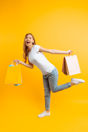 Full length portrait of a smiling young girl with bags in her hands, the girl is in a hurry for shopping on a yellow background