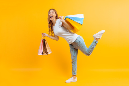 Full length portrait of an enthusiastic young girl with bags in hands, happy girl after shopping on yellow background