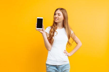 Portrait of a beautiful girl in a white T-shirt, showing a blank screen phone on a yellow background