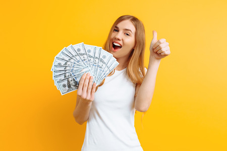 Portrait of a happy contented girl in white t-shirt holding a pile of banknotes and looking at the camera on a yellow background