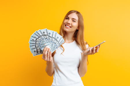 Portrait of an excited woman in white t-shirt showing money bills and holding mobile phone isolated on yellow background