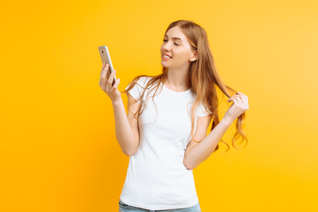 Beautiful young woman in a white T-shirt, uses a mobile phone, for messaging, looks at the screen of a smartphone, on a yellow background 스톡 콘텐츠