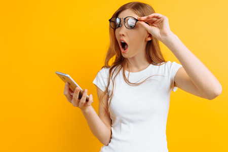 Surprised girl with glasses looks shocked at the phone on a yellow background