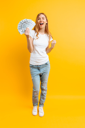 Portrait of happy contented girl in white t-shirt with a bunch of banknotes and celebrating victory and success over yellow background
