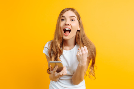 Cheerful girl in a white T-shirt holding a mobile phone, celebrates the victory and success on a yellow background 스톡 콘텐츠