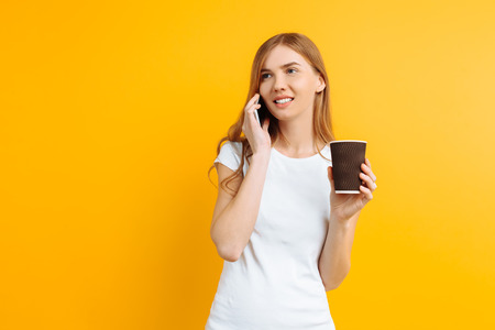 Portrait of a young beautiful woman in a white T-shirt, talking on the phone and holding a glass of coffee in her hands, on a yellow background