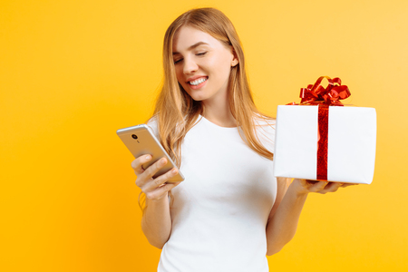 Portrait of smiling attractive woman, in white T-shirt, holding gift box, standing and using mobile phone, isolated on yellow background
