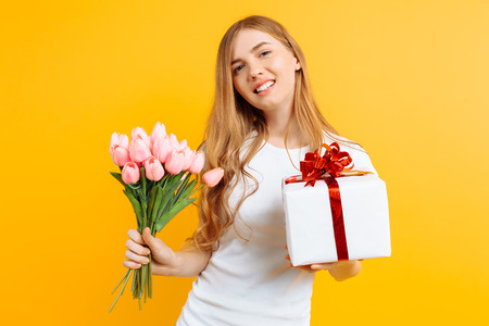 Happy girl in a white T-shirt holding a bouquet of beautiful flowers and a gift box on a yellow background. Stock Photo