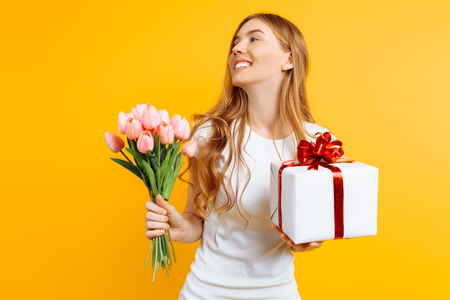 Happy girl in a white T-shirt holding a bouquet of beautiful flowers and a gift box on a yellow background. 스톡 콘텐츠