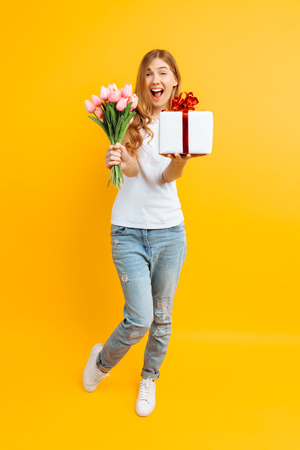 Full length, enthusiastic girl screaming with happiness in a white T-shirt with a bouquet of beautiful flowers and a gift box on a yellow background. Stock Photo