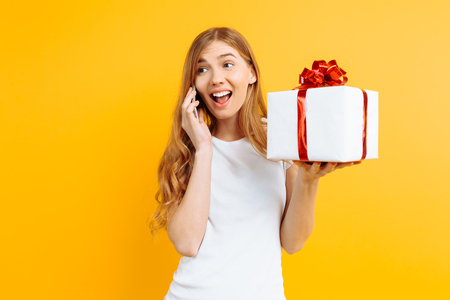 Happy young woman, wearing a white t-shirt, talking on a mobile phone, shows a gift box, on a yellow background