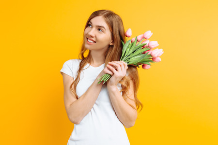 Happy thoughtful girl in a white T-shirt, holding a bouquet of flowers in hand, on a yellow background