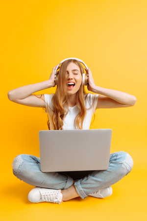 An image of a beautiful woman in a white T-shirt listening to music on headphones using a laptop while sitting cross-legged on a yellow background