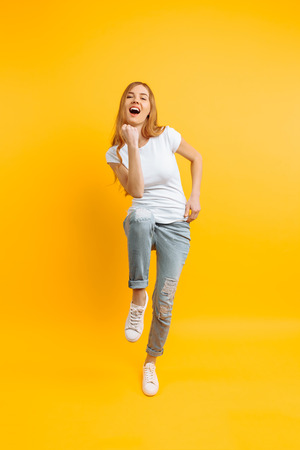 Full length, enthusiastic girl in a white T-shirt, celebrating success on a yellow background 스톡 콘텐츠