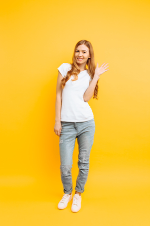 Full length, positive girl in a white T-shirt, shows a greeting gesture, on a yellow background