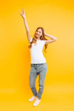 Full length, positive girl in a white T-shirt, shows a peaceful gesture, two fingers, on a yellow background 스톡 콘텐츠
