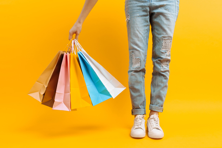 Close up image of legs, woman after shopping stands with lots of multi-colored bags, on yellow background 스톡 콘텐츠