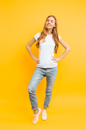 Full length portrait of a cheerful beautiful girl in white t-shirt, posing on a yellow background