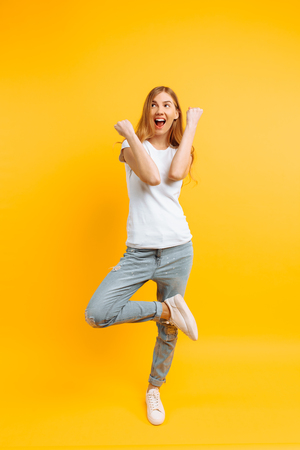 Full length, enthusiastic girl in a white T-shirt, celebrating success on a yellow background Stock Photo