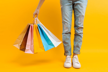 Close up image of legs, woman after shopping stands with lots of multi-colored bags, on yellow background Stock Photo