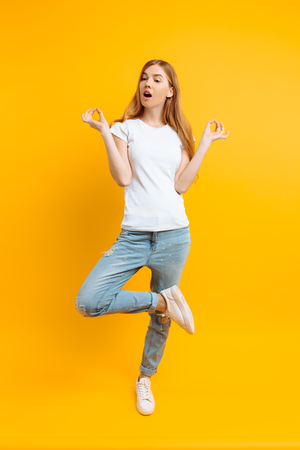 Full length, cheerful girl in a white T-shirt is meditating in a good mood, on a yellow background