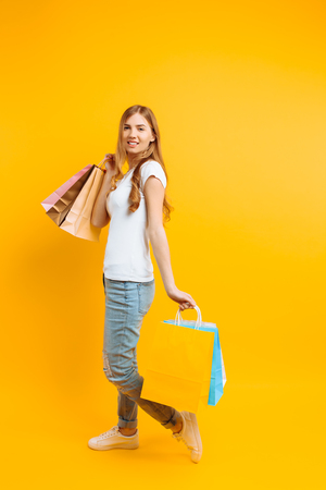Full-length portrait of a young beautiful woman in a white T-shirt, with multi-colored bags, on a yellow background