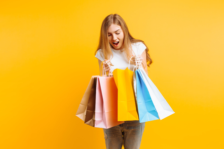 Portrait of a curious young woman in a white T-shirt, after a good shopping, looking inside the bag, isolated on a yellow background Stock Photo