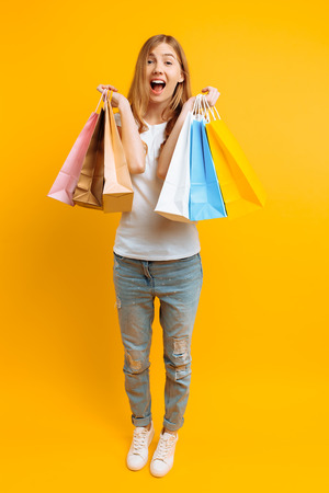 Full-length portrait of a young shocked woman in a white T-shirt, happy after shopping with multi-colored bags, on a yellow background 스톡 콘텐츠