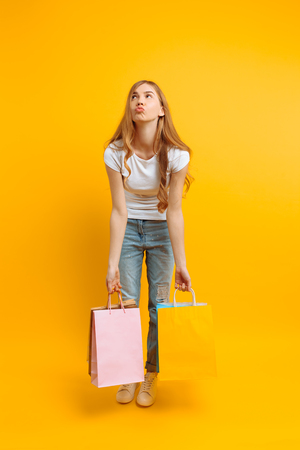 Full length girl feels tired from shopping, a woman with lots of bags, beautiful girl holding bags on a yellow background