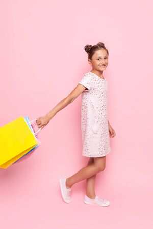 Beautiful teenage girl in stylish dress with packages in hand makes a purchase, on a pink background