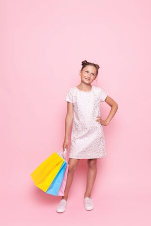 Beautiful teenage girl in stylish dress with packages in hand makes a purchase, on a pink background Stockfoto - 129392858