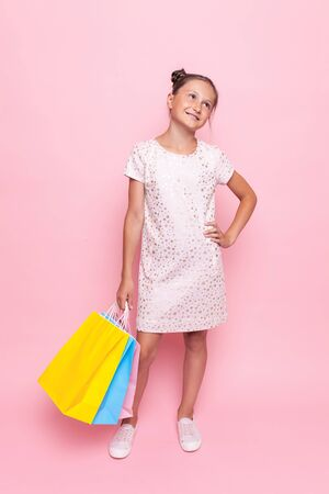 Beautiful teenage girl in stylish dress with packages in hand makes a purchase, on a pink background Stockfoto - 129392851