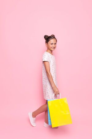 Beautiful teenage girl in stylish dress with packages in hand makes a purchase, on a pink background Stockfoto