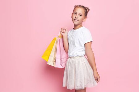 Happy girl in stylish dress, teenager with purchases in hands, after shopping trip Stockfoto
