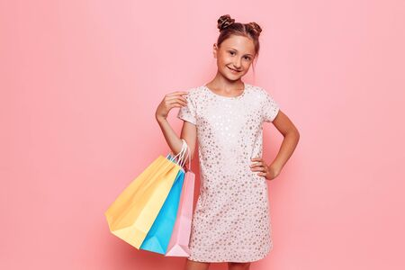 Happy girl in stylish dress, teenager with purchases in hand, after a shopping trip on a pink background Stockfoto