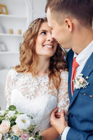 Beautiful bride in white dress and groom in suit, posing in white Studio interior, wedding style trends
