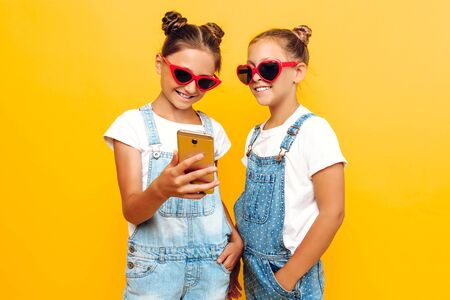 Two teenage girls in sunglasses holding a smartphone in their hands and looking at the screen, on a yellow background