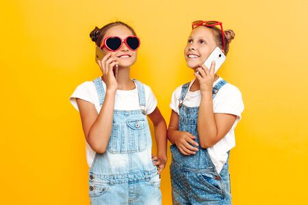 Two teenage girls in dark glasses holding a smartphone in their hands and talking on the phone, on a yellow background