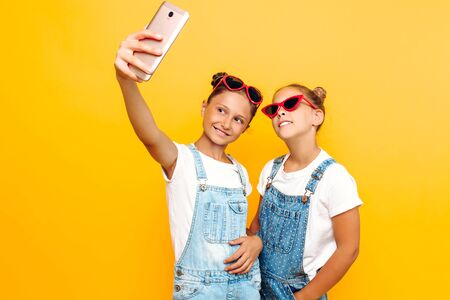 Two teenage girls in sunglasses are resting and taking a selfie on a smartphone on a yellow background.