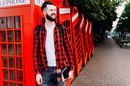 Stylish man with a beard, hipster dressed in a white T-shirt and a plaid shirt, a man holding a skateboard in his hands and posing in front of a red telephone box Stock Photo