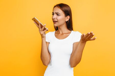 Angry young woman says irritated cell phone to hear bad news via the phone. Portrait of a girl with a mobile phone, on a yellow background